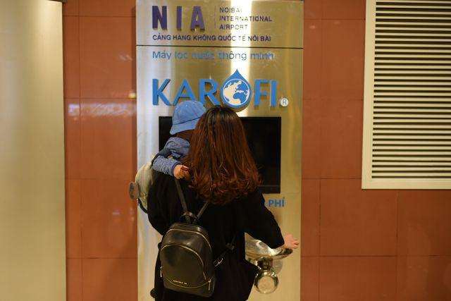 Hành khách đang lấy nước uống tinh khiết miễn phí từ bốt nước tại sân bay Nội Bài.